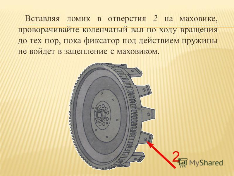 Вставляя ломик в отверстия 2 на маховике, проворачивайте коленчатый вал по ходу вращения до тех пор, пока фиксатор под действием пружины не войдет в зацепление с маховиком. 2
