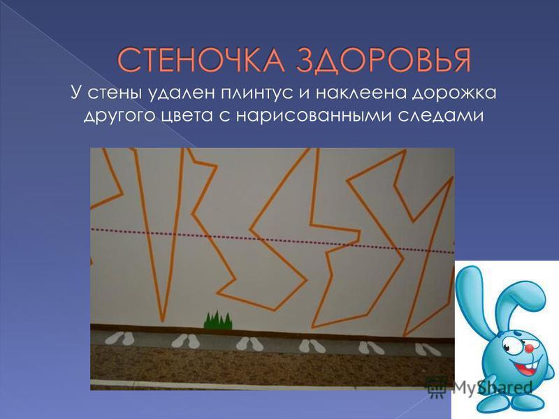 У стены удален плинтус и наклеена дорожка другого цвета с нарисованными следами