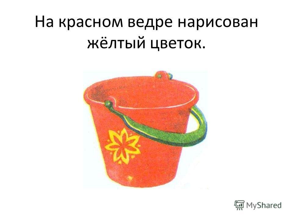 На красном ведре нарисован жёлтый цветок.
