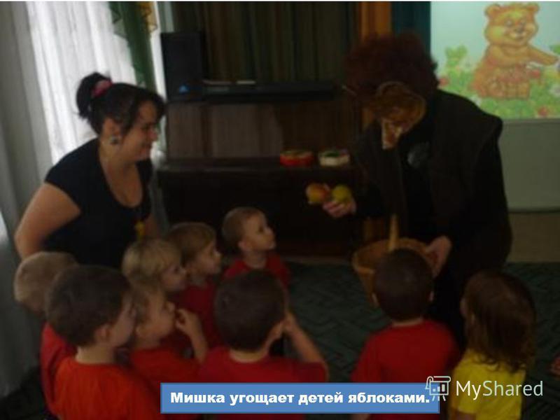 Мишка угощает детей яблоками.