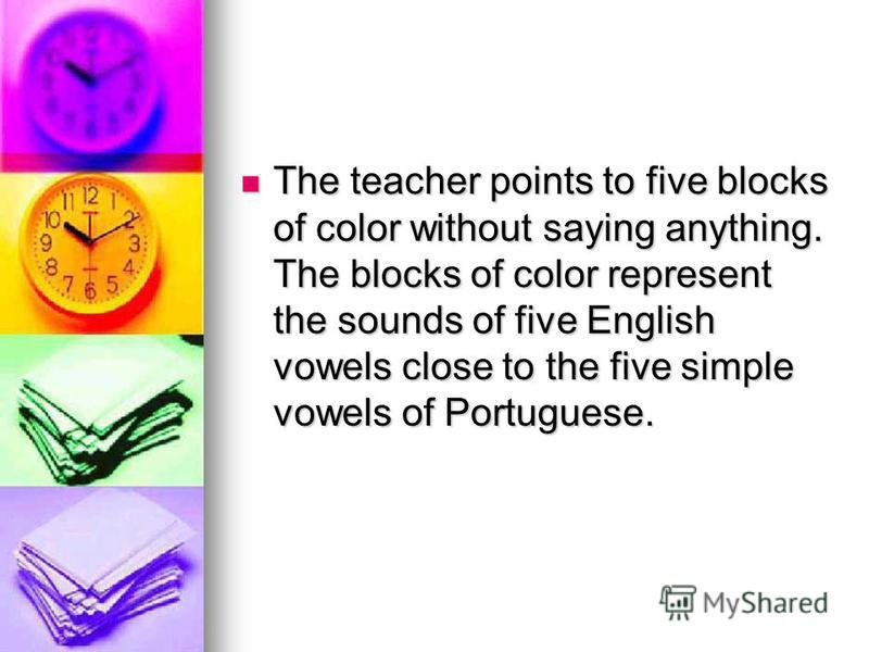 The teacher points to five blocks of color without saying anything. The blocks of color represent the sounds of five English vowels close to the five simple vowels of Portuguese. The teacher points to five blocks of color without saying anything. The