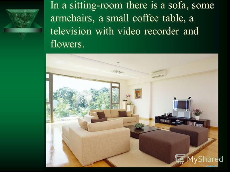 In a sitting-room there is a sofa, some armchairs, a small coffee table, a television with video recorder and flowers.