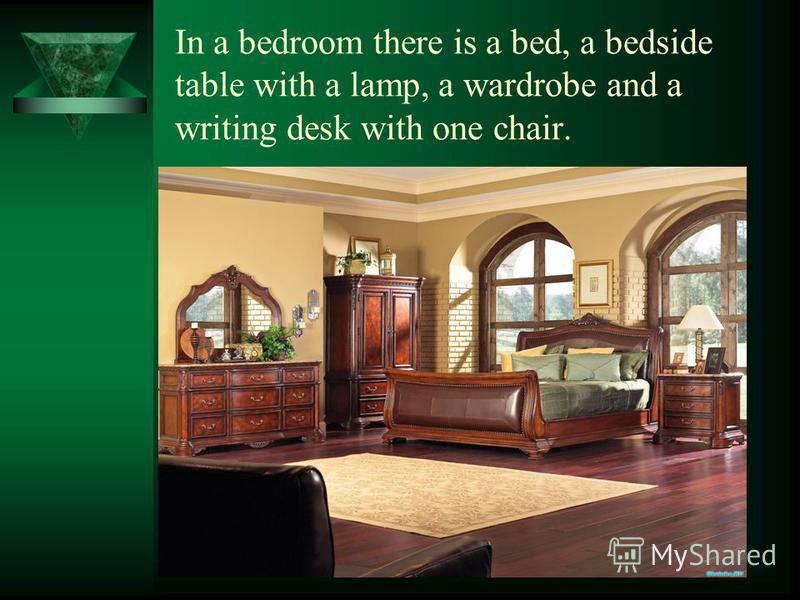 In a bedroom there is a bed, a bedside table with a lamp, a wardrobe and a writing desk with one chair.