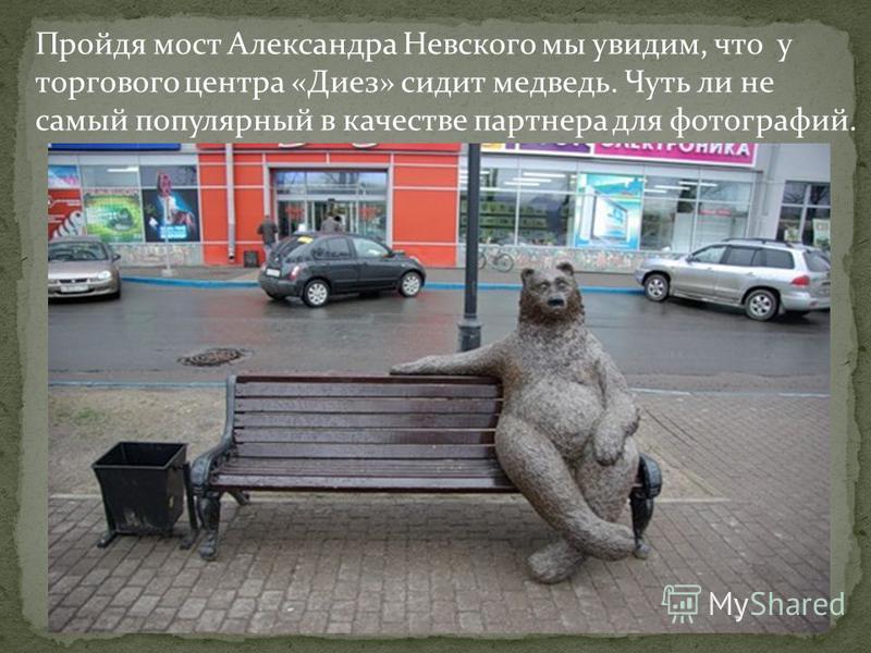 Пройдя мост Александра Невского мы увидим, что у торгового центра «Диез» сидит медведь. Чуть ли не самый популярный в качестве партнера для фотографий.