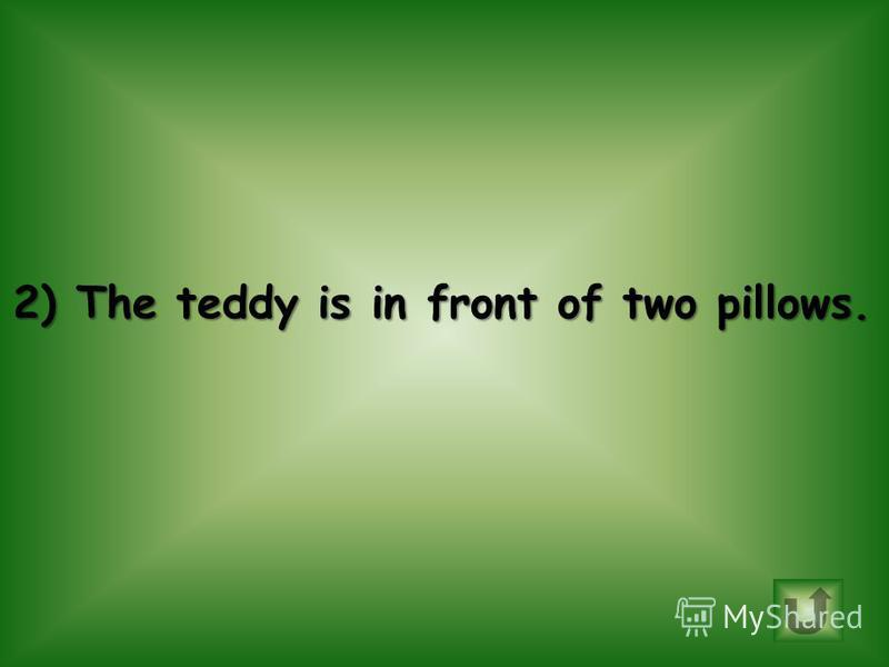 Choose correct sentence. 1.The duck is on the floor. 2.The teddy is in front of two pillows.