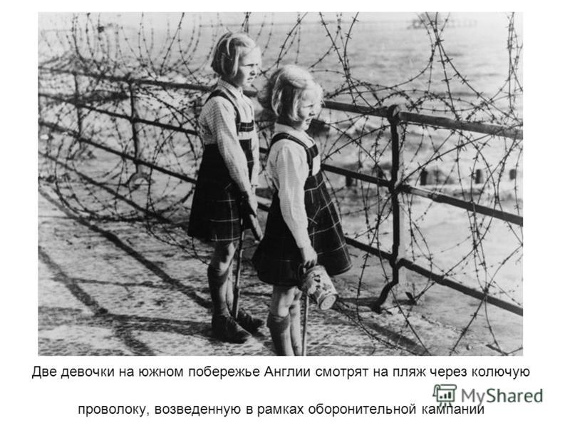 Две девочки на южном побережье Англии смотрят на пляж через колючую проволоку, возведенную в рамках оборонительной кампании