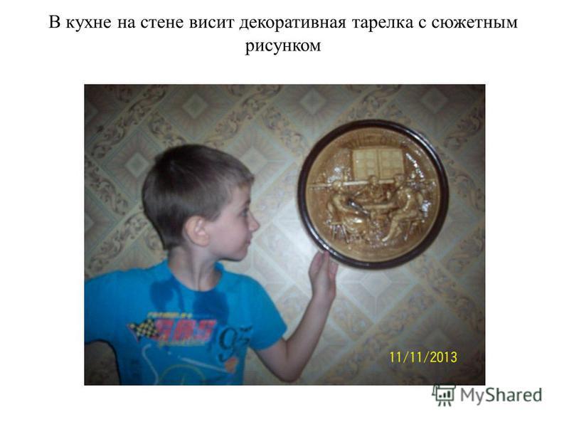 В кухне на стене висит декоративная тарелка с сюжетным рисунком