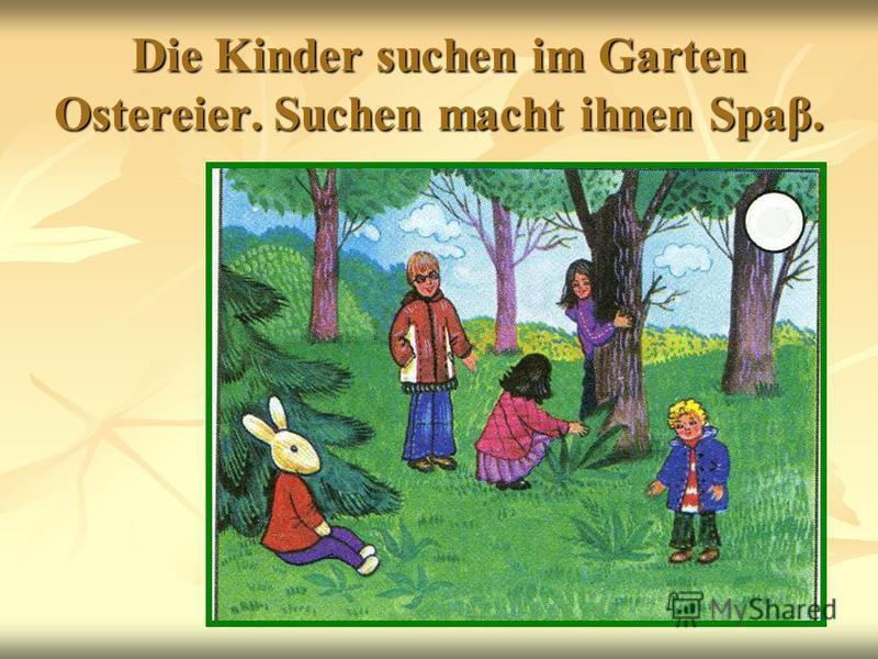 Die Kinder suchen im Garten Ostereier. Suchen macht ihnen Spaβ.