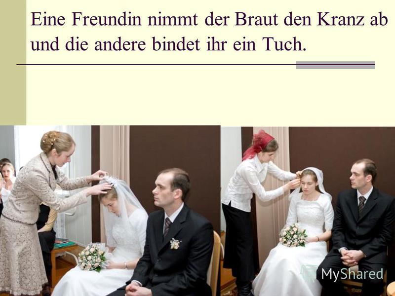 Eine Freundin nimmt der Braut den Kranz ab und die andere bindet ihr ein Tuch.