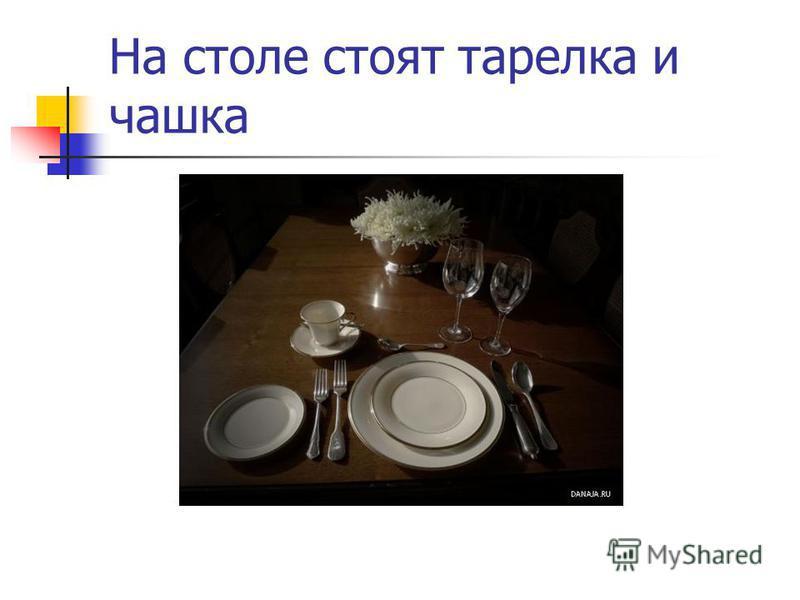 На столе стоят тарелка и чашка