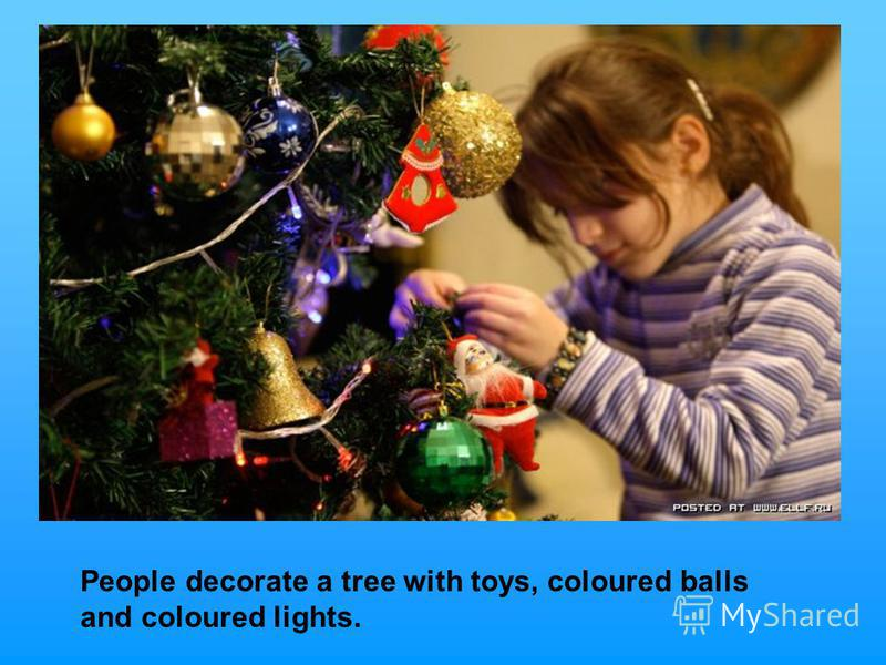 People decorate a tree with toys, coloured balls and coloured lights.