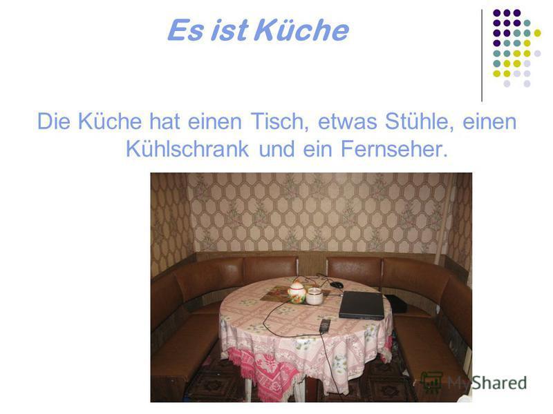 Es ist Küche Die Küche hat einen Tisch, etwas Stühle, einen Kühlschrank und ein Fernseher.