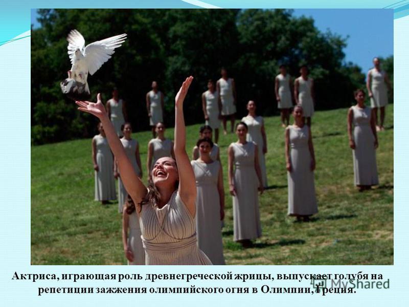Актриса, играющая роль древнегреческой жрицы, выпускает голубя на репетиции зажжения олимпийского огня в Олимпии, Греция.