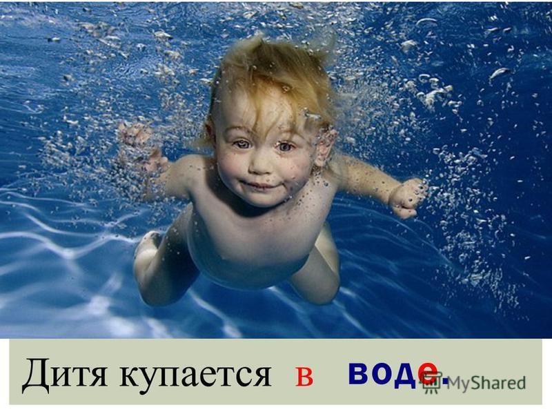 Дитя купается в воде.