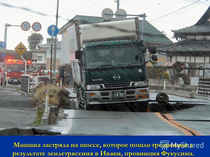 Машина застряла на шоссе, которое пошло трещинами в результате землетрясения в Иваки, провинция Фукусима.