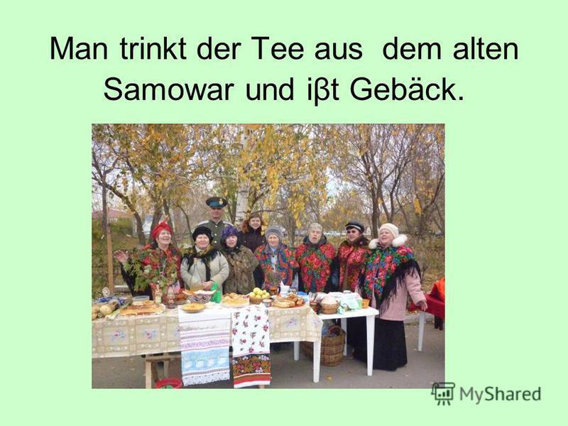 Man trinkt der Tee aus dem alten Samowar und iβt Gebäck.