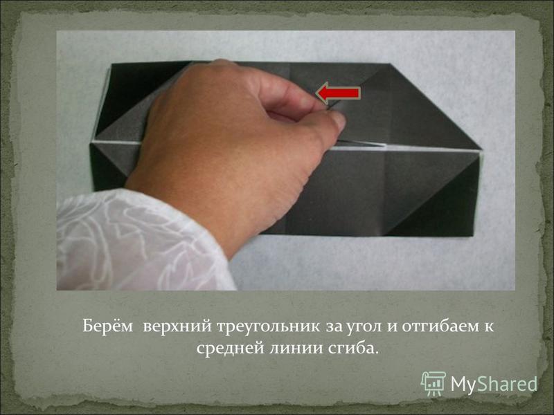 Берём верхний треугольник за угол и отгибаем к средней линии сгиба.