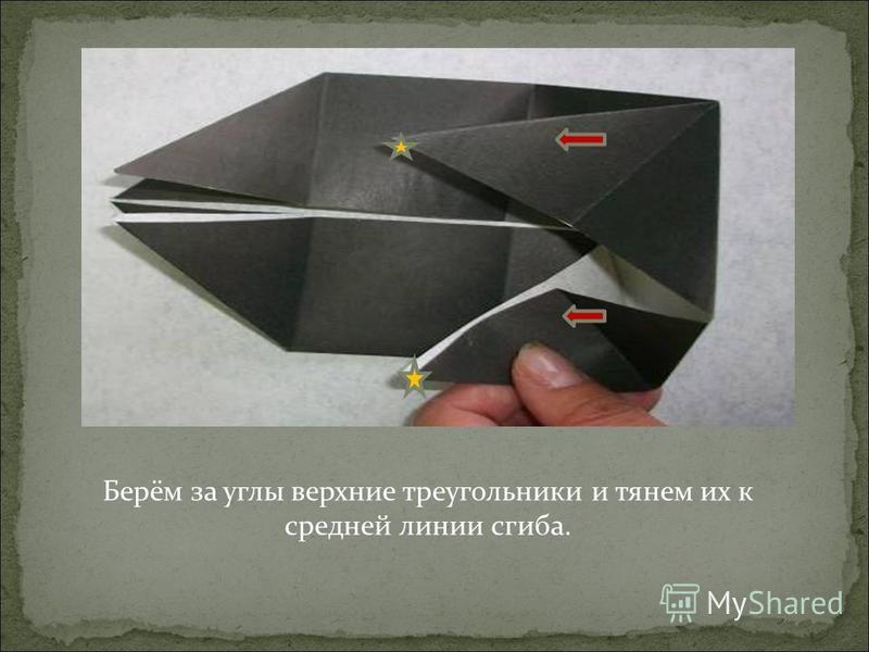 Берём за углы верхние треугольники и тянем их к средней линии сгиба.
