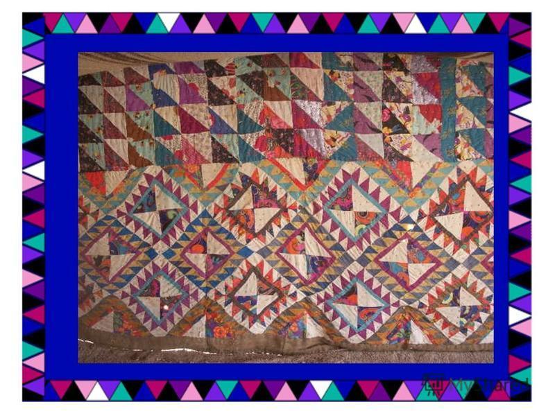 Выполнена в технике шитья треугольниками – из них собраны квадраты, которые сшиты в полотно. Отделка – двухцветные полосы, сшитые приемом «под рамку».
