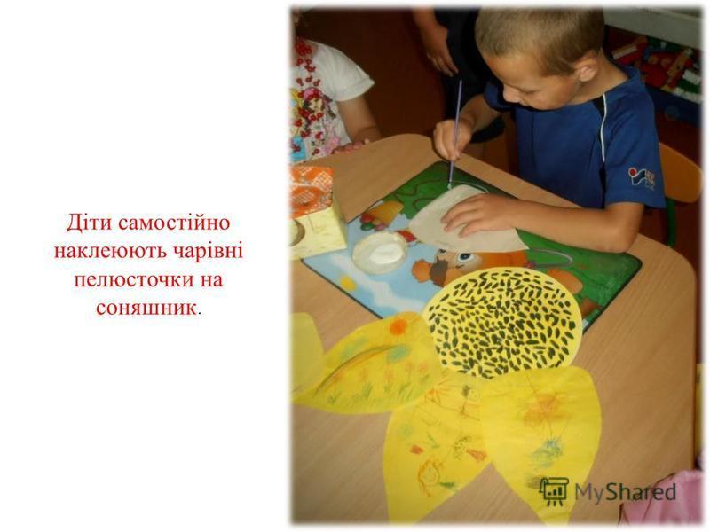 Діти самостійно наклеюють чарівні пелюсточки на соняшник.