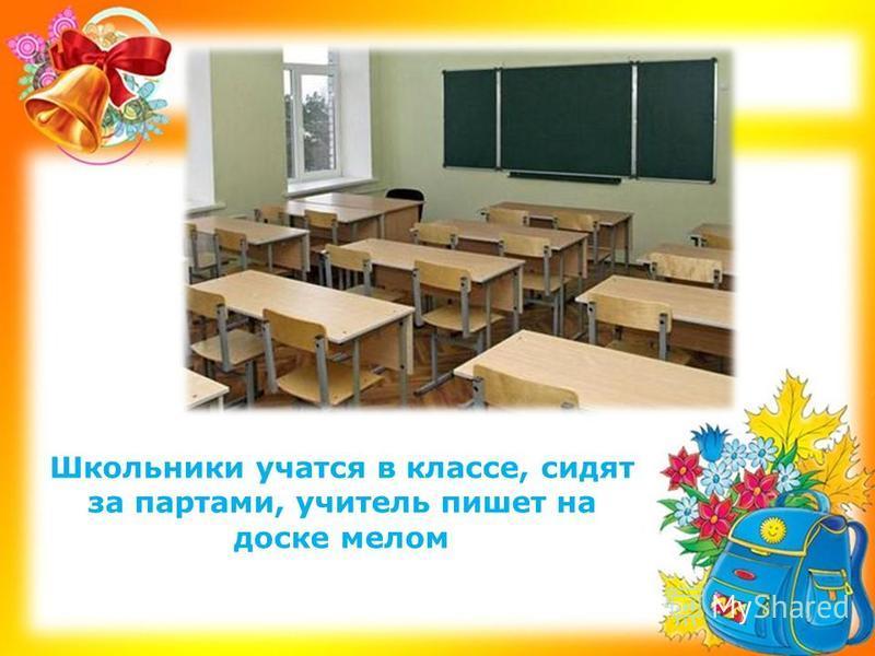 Школьники учатся в классе, сидят за партами, учитель пишет на доске мелом