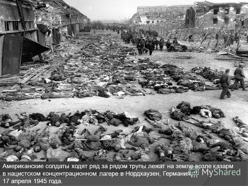 Американские солдаты ходят ряд за рядом трупы лежат на земле возле казарм в нацистском концентрационном лагере в Нордхаузен, Германия, 17 апреля 1945 года.