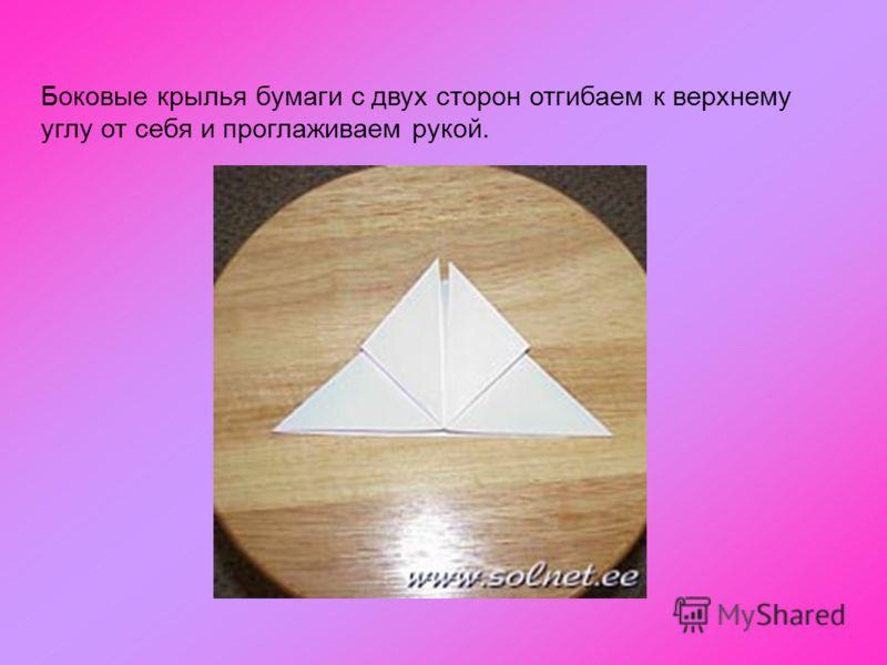Боковые крылья бумаги с двух сторон отгибаем к верхнему углу от себя и проглаживаем рукой.