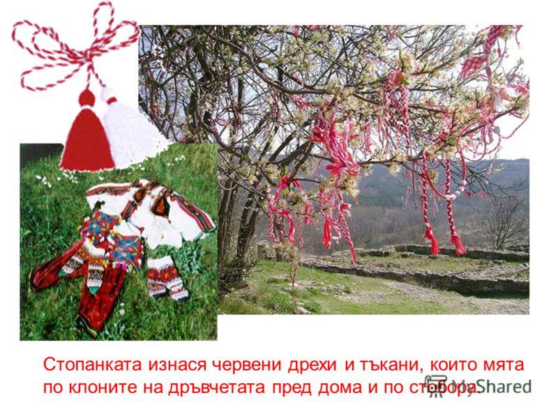 Стопанката изнася червени дрехи и тъкани, които мята по клоните на дръвчетата пред дома и по стобора.