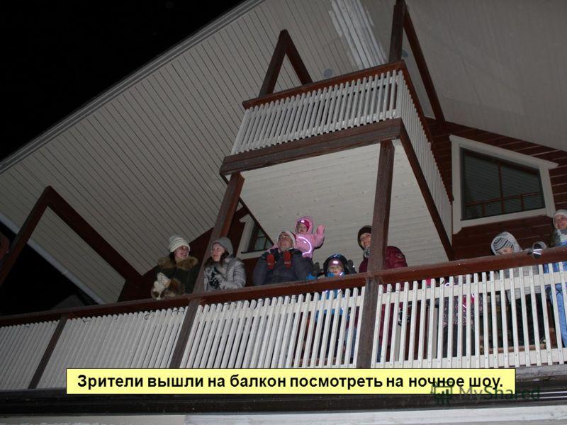 Зрители вышли на балкон посмотреть на ночное шоу.