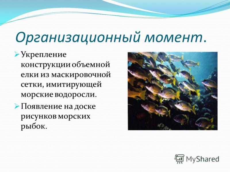 Организационный момент. Укрепление конструкции объемной елки из маскировочной сетки, имитирующей морские водоросли. Появление на доске рисунков морских рыбок.