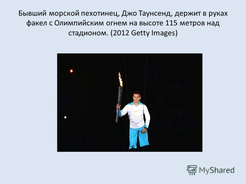 Бывший морской пехотинец, Джо Таунсенд, держит в руках факел с Олимпийским огнем на высоте 115 метров над стадионом. (2012 Getty Images)