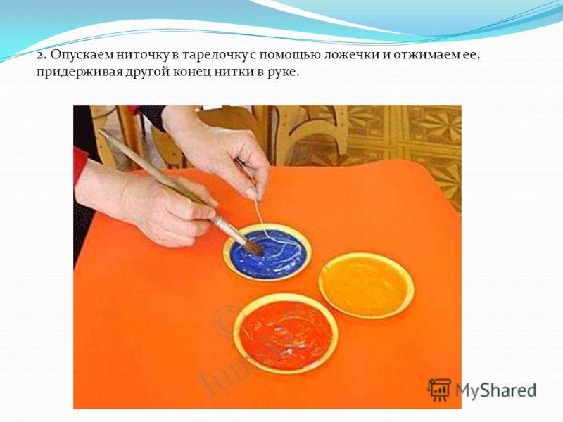 2. Опускаем ниточку в тарелочку с помощью ложечки и отжимаем ее, придерживая другой конец нитки в руке.