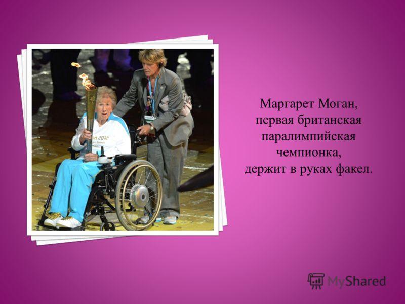 Маргарет Моган, первая британская паралимпийская чемпионка, держит в руках факел.