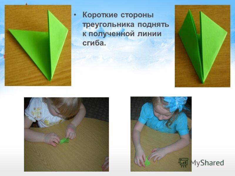 Короткие стороны треугольника поднять к полученной линии сгиба.