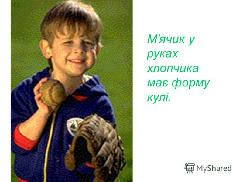 Мячик у руках хлопчика має форму кулі.