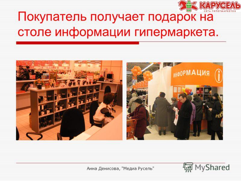 Анна Денисова, Медиа Русель Покупатель получает подарок на столе информации гипермаркета.