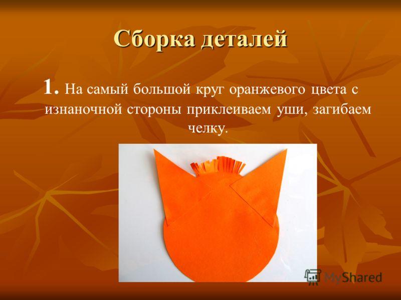 Сборка деталей 1. На самый большой круг оранжевого цвета с изнаночной стороны приклеиваем уши, загибаем челку.
