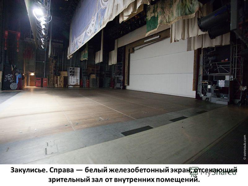 Закулисье. Справа белый железобетонный экран, отсекающий зрительный зал от внутренних помещений.