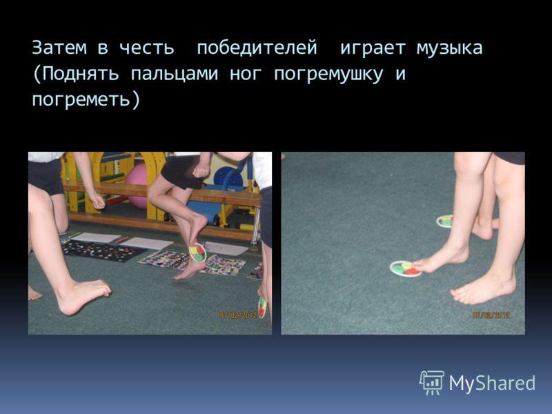 Затем в честь победителей играет музыка (Поднять пальцами ног погремушку и погреметь)