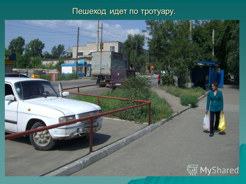 Пешеход идет по тротуару.