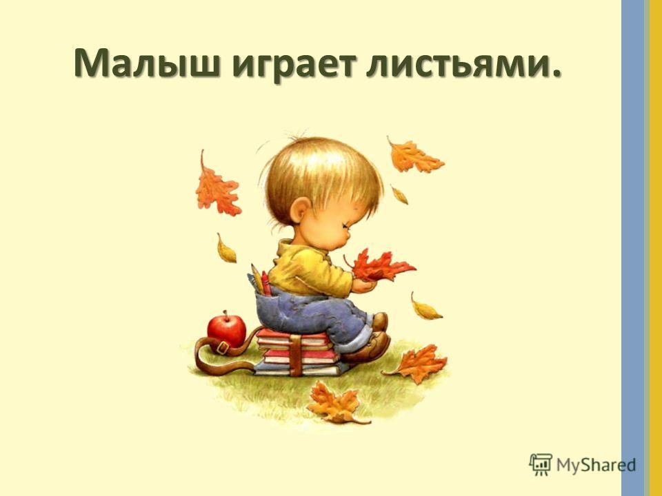 Малыш играет листьями.