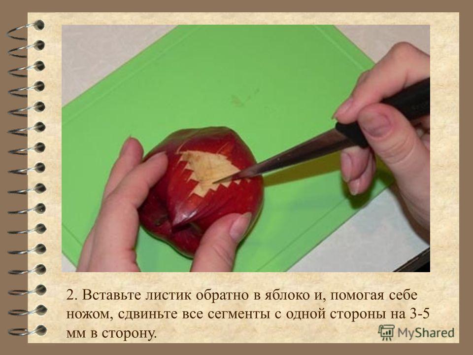 2. Вставьте листик обратно в яблоко и, помогая себе ножом, сдвиньте все сегменты с одной стороны на 3-5 мм в сторону.