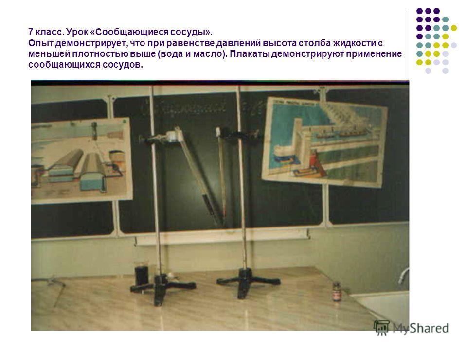 7 класс. Урок «Сообщающиеся сосуды». Опыт демонстрирует, что при равенстве давлений высота столба жидкости с меньшей плотностью выше (вода и масло). Плакаты демонстрируют применение сообщающихся сосудов.