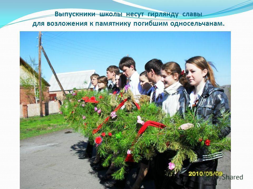 Выпускники школы несут гирлянду славы для возложения к памятнику погибшим односельчанам.