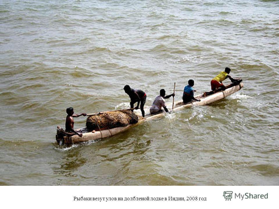Рыбаки везут улов на долбленой лодке в Индии, 2008 год