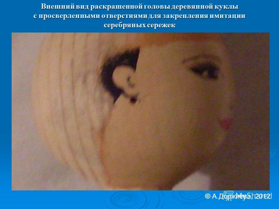 Внешний вид раскрашенной головы деревянной куклы с просверленными отверстиями для закрепления имитации серебряных сережек © А.Доржиева, 2012