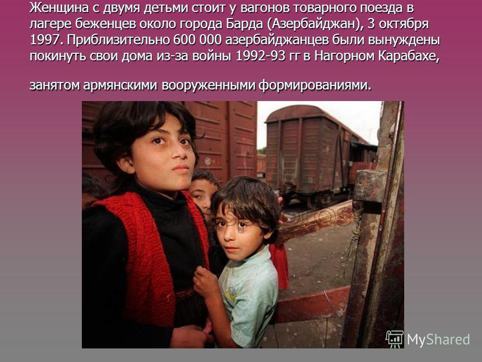 Женщина с двумя детьми стоит у вагонов товарного поезда в лагере беженцев около города Барда (Азербайджан), 3 октября 1997. Приблизительно 600 000 азербайджанцев были вынуждены покинуть свои дома из-за войны 1992-93 гг в Нагорном Карабахе, занятом ар
