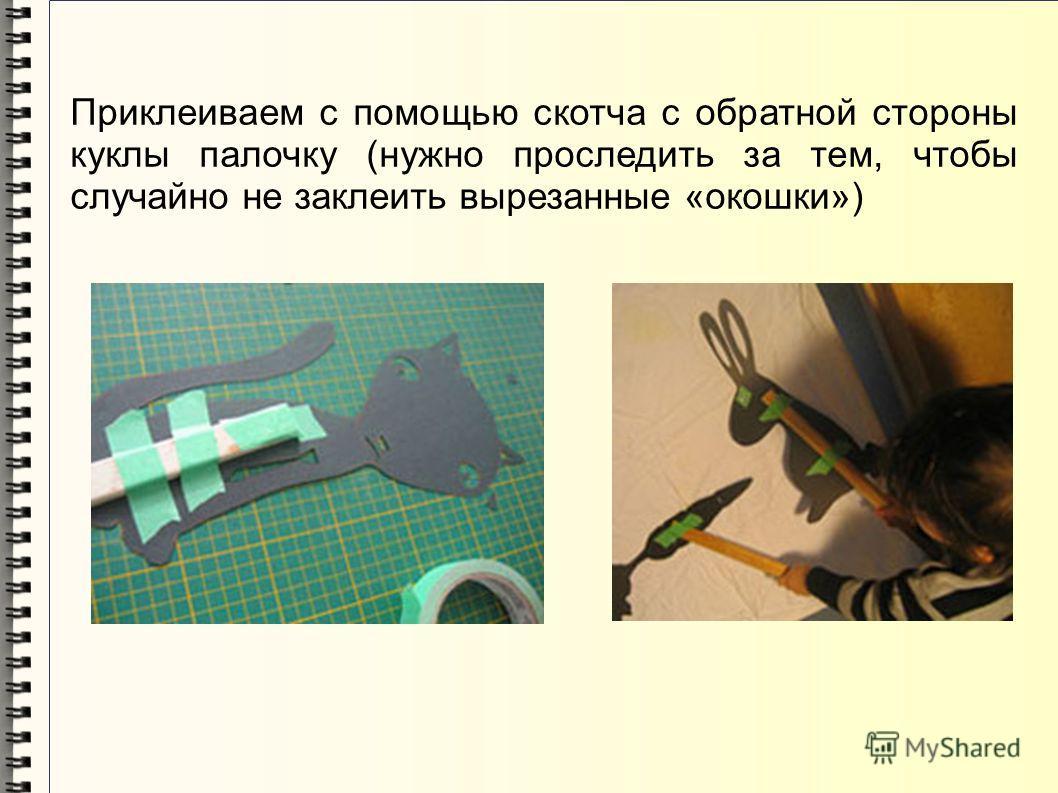 Приклеиваем с помощью скотча с обратной стороны куклы палочку (нужно проследить за тем, чтобы случайно не заклеить вырезанные «окошки»)