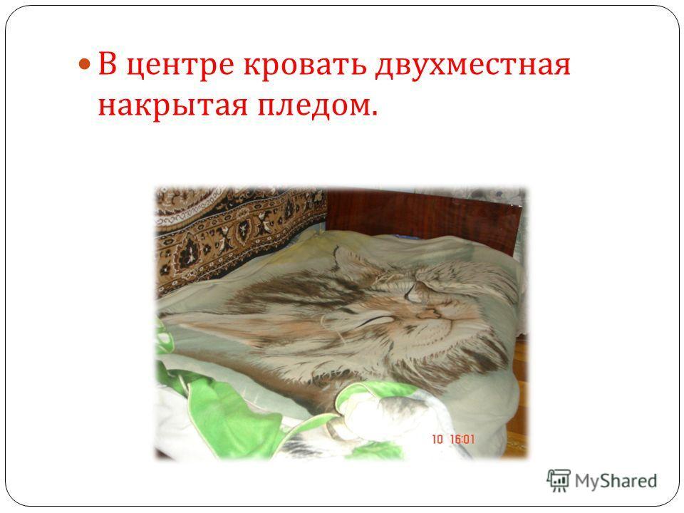 В центре кровать двухместная накрытая пледом.