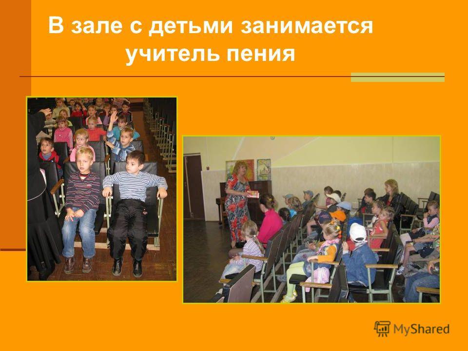 В зале с детьми занимается учитель пения